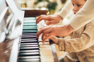 boy in white long sleeve shirt playing piano