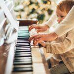 boy in white long sleeve shirt playing piano